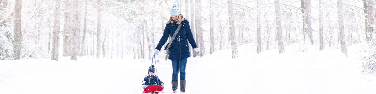 Photographie d'une femme se promenant dans le bois en hiver avec son fils.